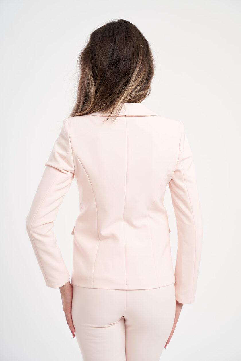 Costum roz din două piese: Un sacou cu un singur nasture, îmbrăcat manual, și pantaloni eleganți în culoare. Cusături descălcate pentru un aspect impecabil. Pantalonii au o cusătură de ștafir în partea de jos pentru a continua aspectul curat al sacoului.