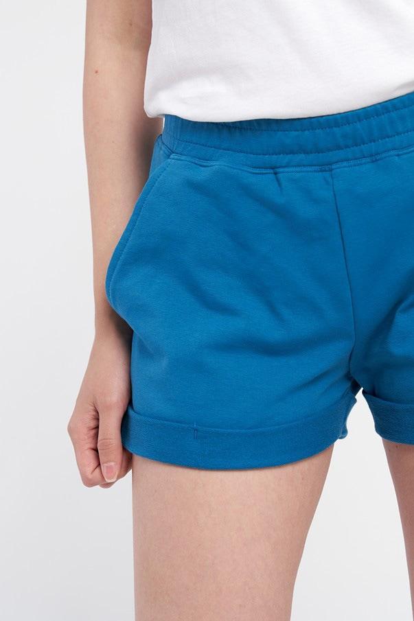 Pantaloni scurți albastri de damă cu buzunar la spate și betelie elastică. Pantalonii sunt fabricați din bumbac organic și au manșeta întoarsă în partea de jos.