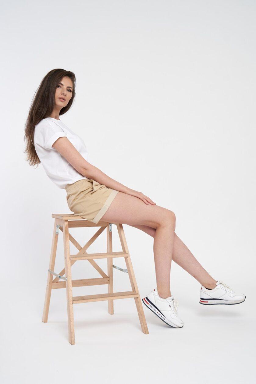 Pantaloni scurți crem de damă cu buzunar la spate și betelie elastică. Pantalonii sunt fabricați din bumbac organic și au manșeta întoarsă în partea de jos.